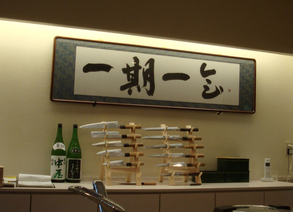 Sushi knives and calligraphy above the bar.